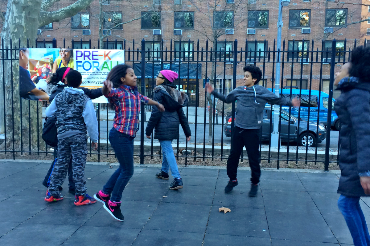 Middle school students jumping and playing in a Brooklyn schoolyard.
