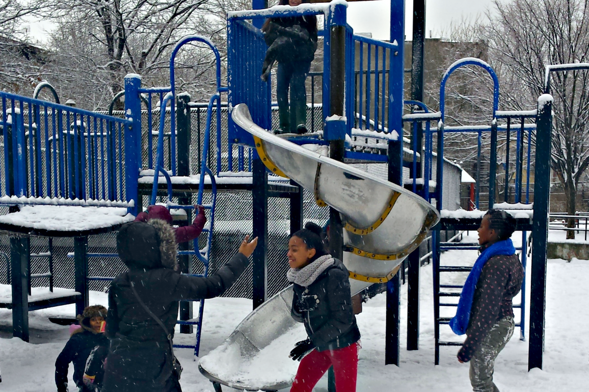 Kids playing on the snowy jungle gym.