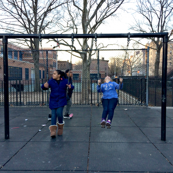 Middle schoolers swinging with the chain-linked schoolyard fences in the background.